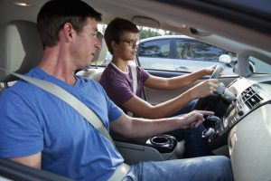 Teenager (15 years) with driving instructor (40s).